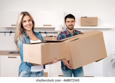 Portrait of beautiful and young couple with boxes moving in new home