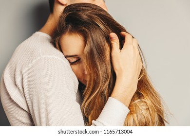 Portrait of beautiful young couple in casual clothes hugging, on gray background