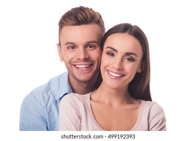 Portrait of beautiful young couple hugging, looking at camera and smiling, isolated on white