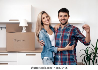 Portrait of beautiful young couple with keys looking at camera.Kitchen with unpacked box playroom