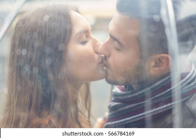 Portrait of Beautiful young couple kissing under a transparent umbrella in a rainy day - Passionate couple kissing under the rain - Boyfriend and girlfriend intimate moments - Focus on girl's eye
