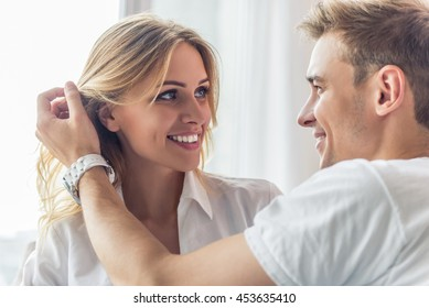 Portrait of beautiful young couple looking at each other and smiling while sitting at home. Man is smoothing his girlfriend's hair