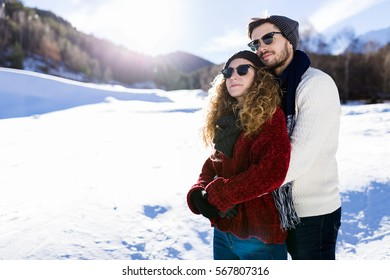 Portrait of beautiful young couple in love over winter background.