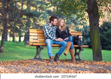 portrait of beautiful young couple sitting on a bech in a park