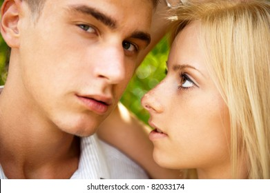 Portrait of beautiful young couple standing against green tree in park relaxing