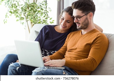 Portrait of beautiful young couple using laptop on the sofa at home.