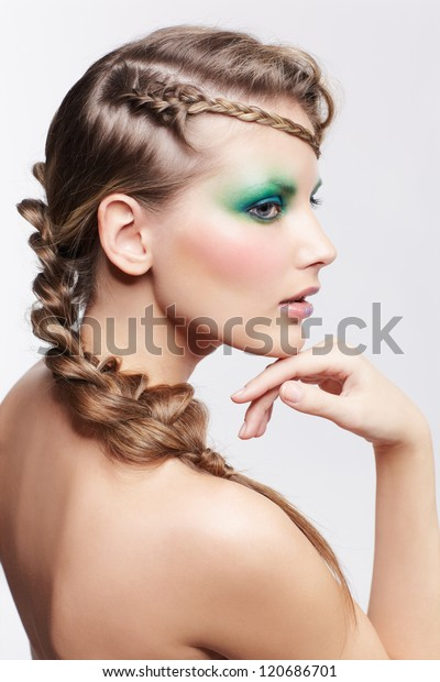 portrait of beautiful young dark blonde woman with creative plait hairdo and green eye shades make up