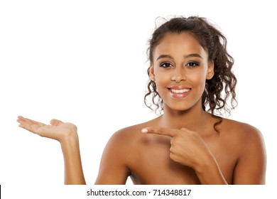 portrait of a beautiful young dark-skinned woman holding imaginary object on a white background