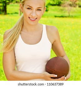 Portrait of beautiful young dressed in white sportswoman with rugby ball, against green of summer park.