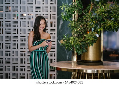 Portrait of a beautiful, young, elegant and confident Indian Asian woman smiling radiantly as she checks her smartphone. She is standing near a marble table with a plant in a stylish interior.