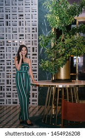 Portrait of a beautiful, young, elegant and confident Indian Asian woman smiling radiantly as she talks on her smartphone. She is standing near a marble table with a plant in a stylish interior.