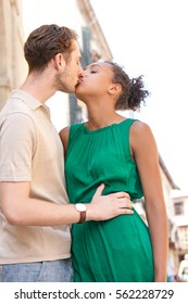 Portrait of beautiful young ethnically diverse couple hugging and kissing in a destination city, romantic passion outdoors. Boyfriend and girlfriend together on holiday, travel recreation lifestyle.