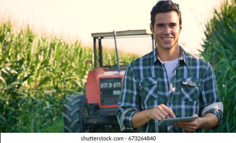 Portrait of a beautiful young farmer (student) working in the field with a tractor working in a tablet, happy, in a shirt, corn field. Concept ecology, transport, farmers, clean air, food, bio product