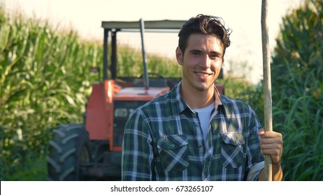 Portrait of a beautiful young farmer (student) working in the field with a tractor, successful smiling, happy, in a shirt, corn field. Concept ecology, transport, farmers, clean air, food, bio product
