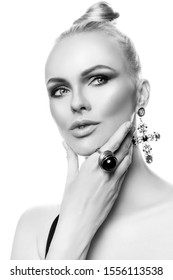Portrait of a beautiful young fashion model woman, white background. Ornaments, bijouterie - large earrings-crosses in Byzantine style. Makeup - studio eyeshadow, black stone ring. Black and white