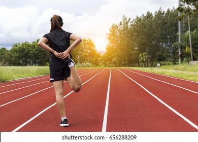 portrait of beautiful young female athlete preparing for running on running track (back view)