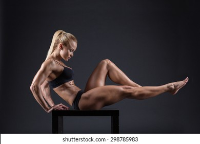 Portrait of a beautiful young female athletes with a dumbbell in studio