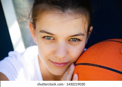 Portrait of a beautiful and young female basketball player with face resting on the ball
