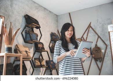 portrait of beautiful young female business owner standing in front of her bag store with tablet