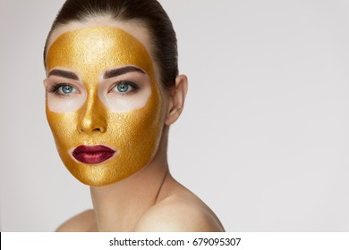 Portrait Of Beautiful Young Female With Cosmetic Gold Mask On Beauty Face.