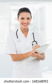 Portrait of a beautiful young female doctor with clipboard standing in the hospital