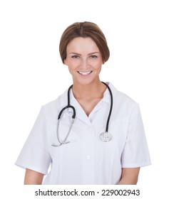 Portrait of beautiful young female doctor smiling over white background