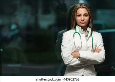 Portrait Of A Beautiful Young Female Doctor Standing Arms Crossed In Office - Successful Woman In Uniform At Work