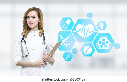 Portrait of a beautiful and young female doctor with a stethoscope and a clipboard standing in a blurred ward. There are blue medicine icons in the background.