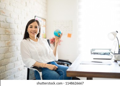 Portrait of beautiful young female entrepreneur holding a globe sitting at her desk and making an eye contact