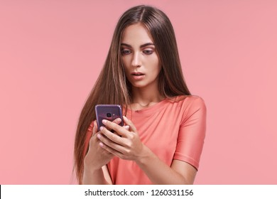 Portrait of beautiful young female looks shocked in smart phone, sees calendar date, finds out that she can`t manage to go on meeting, types message of refusal. People, emotions and technology concept