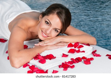 Portrait of beautiful young female lying on massage bed with rose petals in foreground