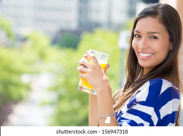 A portrait of a beautiful young female relaxing on a balcony on a sunny day, drinking orange juice, in her new apartment, on a background of a city scenery and green trees. Urban student lifestyle
