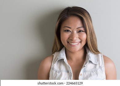 Portrait of a Beautiful young Filipino woman standing on grey background