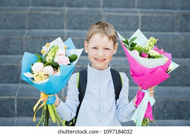Portrait of a beautiful young first-grader with bouquet in a school uniform on the background school. Farewell Bell. day of knowledge. beginning of the school year.