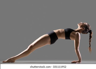 Portrait of beautiful young fit woman in sportswear shorts doing sport exercise, Purvottanasana, Upward Plank posture, shoulders, chest, ankles, arms, wrists, abs, studio image, gray background