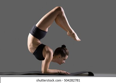 Portrait of beautiful young flexible fit woman in sportswear doing sport exercises on mat, backbend arm stand, Scorpion posture, Vrischikasana, full length, side view, studio image on gray background