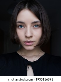 portrait of a beautiful young girl in black with short hair. girl with a square looks at the camera. clear skin. skin care