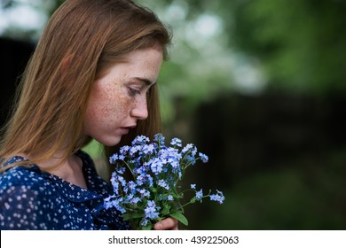 portrait of a beautiful young girl with blue flowers