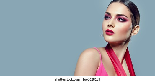 Portrait of a beautiful young girl with bright pink make-up and with pink ribbons in her hands.