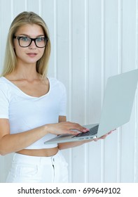 Portrait of a beautiful young girl caucasian girl with blond hair in glasses and a white T-shirt working behind a laptop on a wooden wall background. Concept of business woman.European woman.