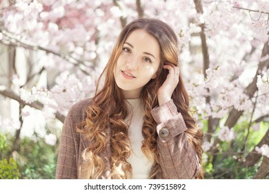 A portrait of a beautiful young girl in a checked coat on the background of pink blooming tree