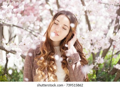 A portrait of a beautiful young girl with closed eyes in a checked coat on the background of pink blooming tree