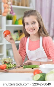 Portrait of beautiful young girl cooking in kitchen at home