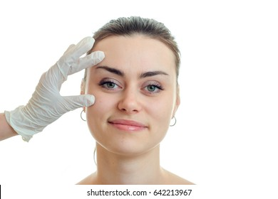 Portrait of a beautiful young girl at a cosmetologist in a white glove close-up