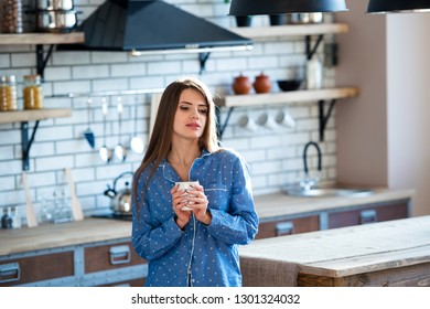 Portrait of a beautiful young girl with a cup of tea or coffee in blue pajamas in the kitchen. Early morning rise - is apledge of energy and health