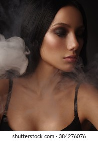 Portrait of the beautiful young girl with dark straight hair, almond-shaped eyes and bronzed perfect covered skin in the black seamless classic bra on the dark background surrounded by the smoke