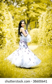 Portrait of beautiful young girl in elegant white dress on autumn park