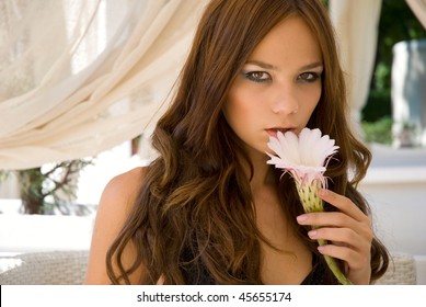 portrait of beautiful young girl with flower in the cafe
