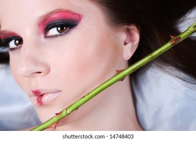 Portrait of beautiful young girl, with the green stem of rose with sharp thorns