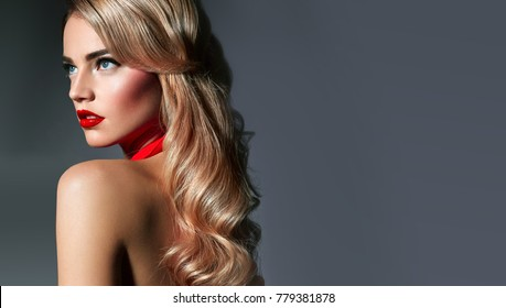 Portrait of a beautiful young girl with hair styling - Hollywood wave in a red dress in studio on a gray background/
